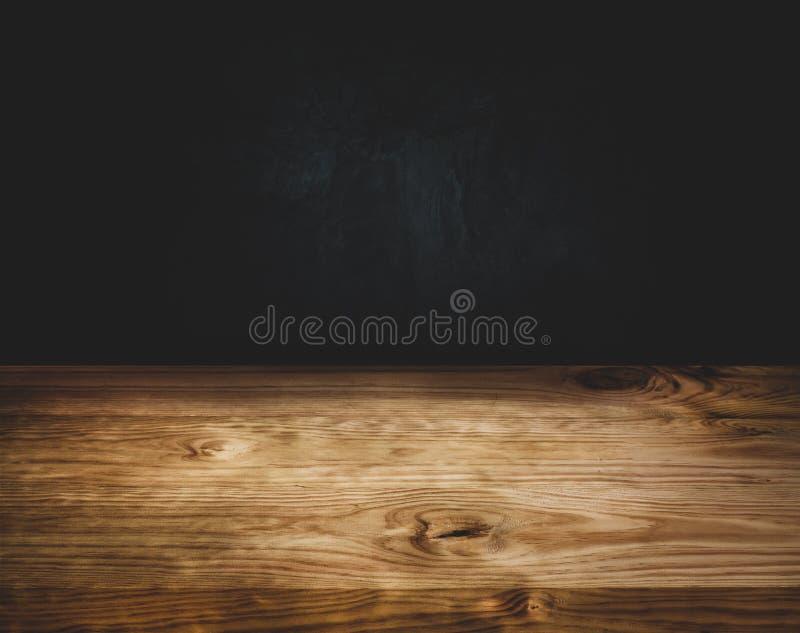 在黑暗的墙壁背景的空的木台式柜台 库存照片