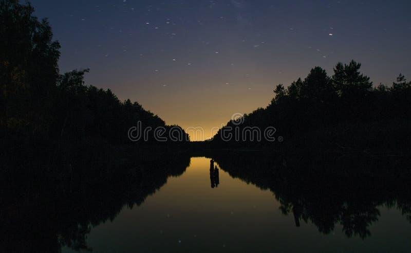 在黑暗的天空中的明亮的日落在河上在森林里 库存照片