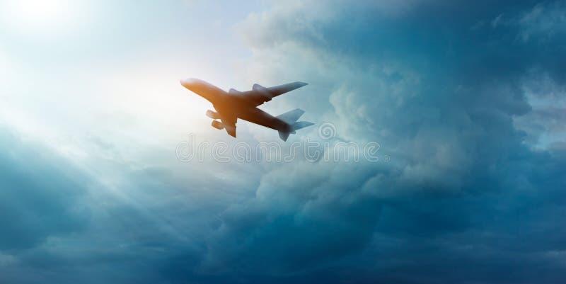 在黑暗的天空和云彩的商业飞机在日出 库存照片