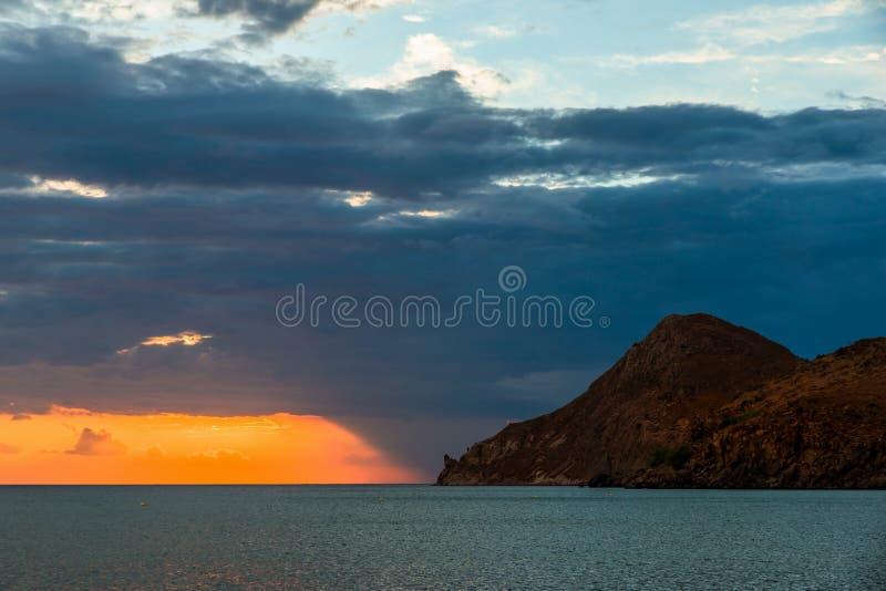 在黑暗的天空和山, LImnos上的橙色日落线 免版税图库摄影