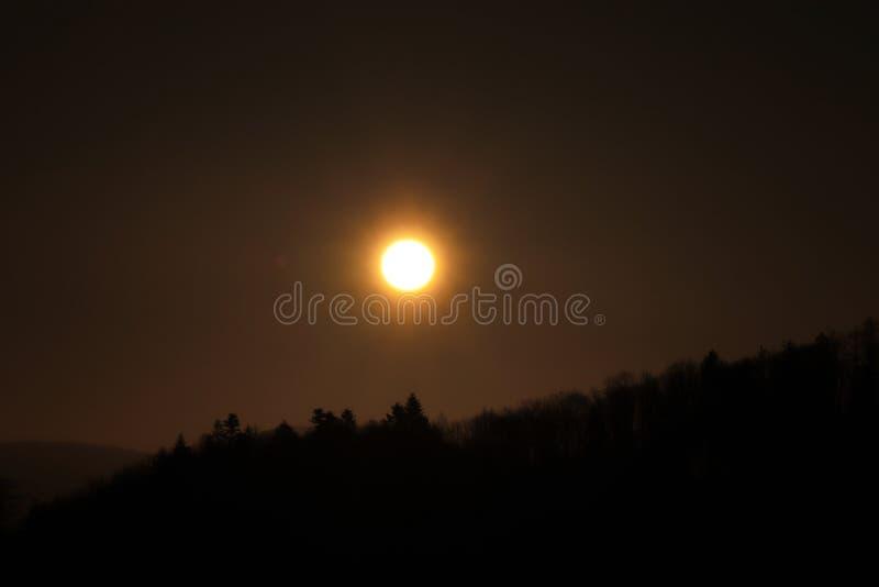 在黑暗的天空的美丽的橙色球与树的阴影 在黑山的日落 太阳的蚀在实时 免版税库存照片