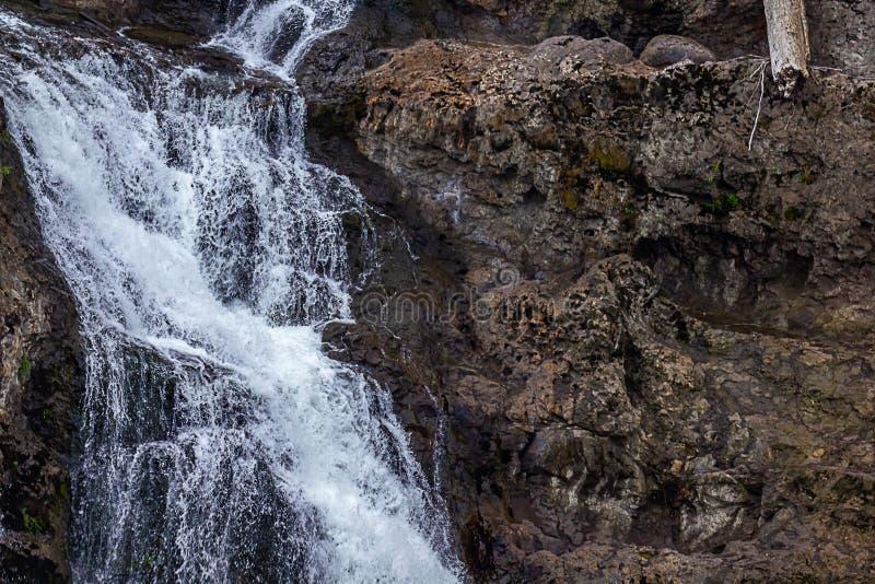 在黑暗的岩石墙壁的小白色瀑布跟斗 免版税库存图片