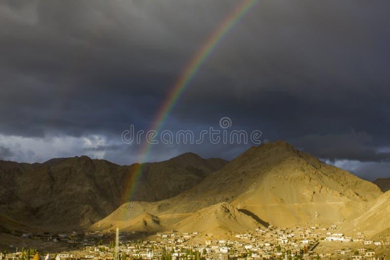 在黑暗的平衡的天空的一条双重彩虹在山沙漠谷的村庄 免版税库存照片