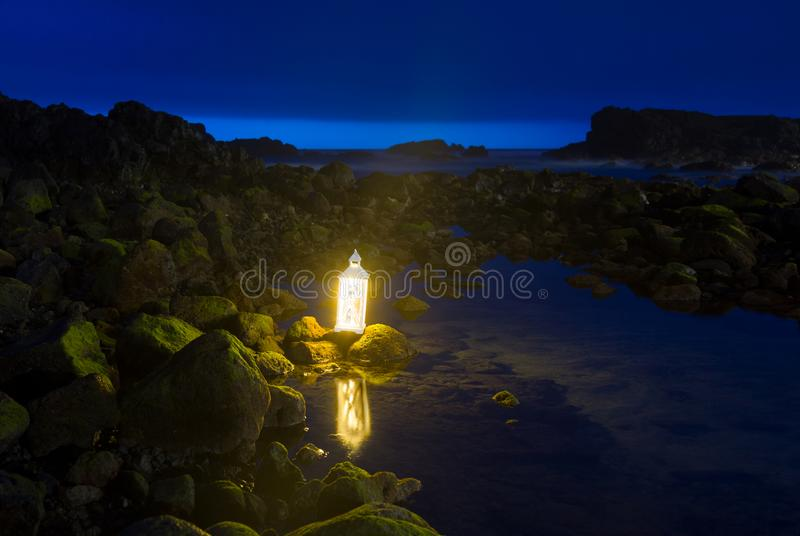 在黑暗的平衡的时间、海边、岩石和仍然水的蓝色小时与在圣地米格尔,亚速尔的一个明亮的灯笼 库存照片