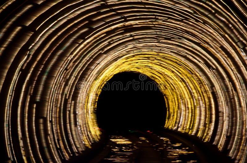 在黑暗的摘要发光的黄灯隧道 免版税图库摄影