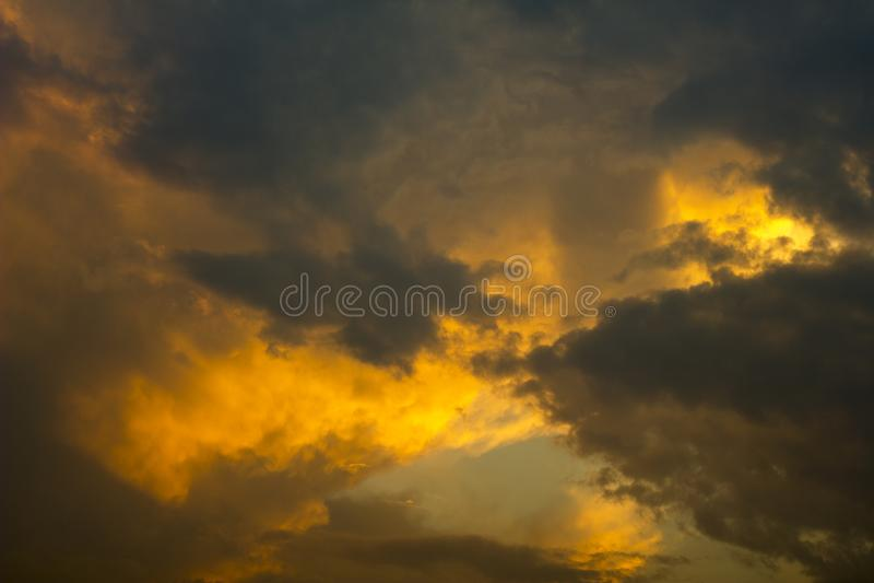 在黑暗的日落天空的明亮的橙色灰色暴风云 在天空的雨云 免版税库存图片