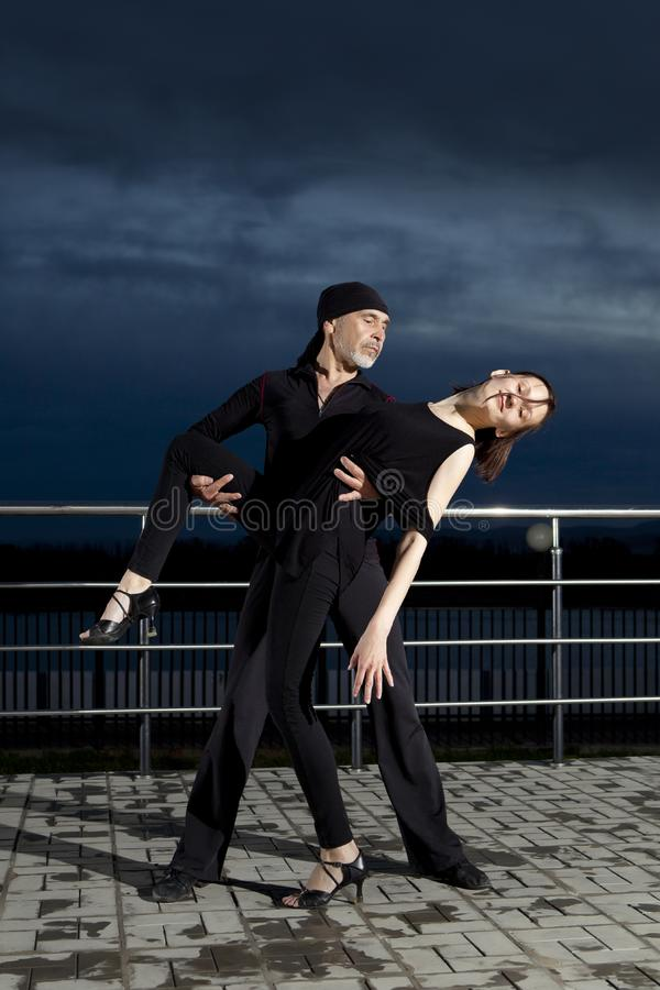 在黑暗的日落的资深夫妇交谊舞 免版税图库摄影