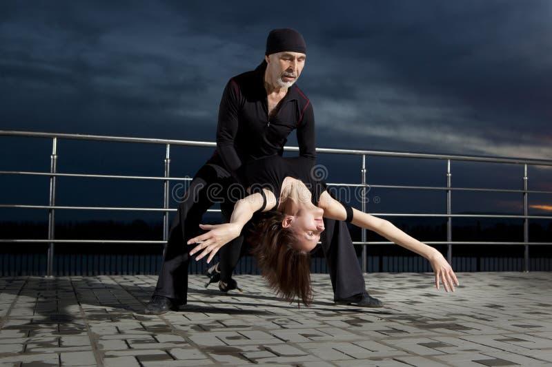 在黑暗的日落的资深夫妇交谊舞 库存照片