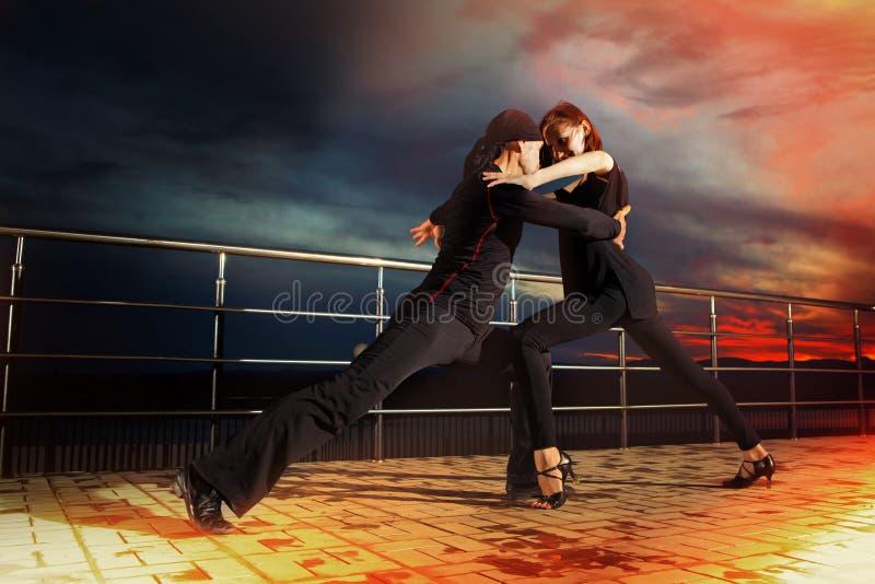 在黑暗的日落的资深夫妇交谊舞 免版税库存图片