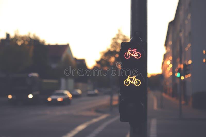 在黑暗的晨光中,经常出现的交叉路口显示红色和黄色自行车标志的自行车道交通灯 免版税库存图片