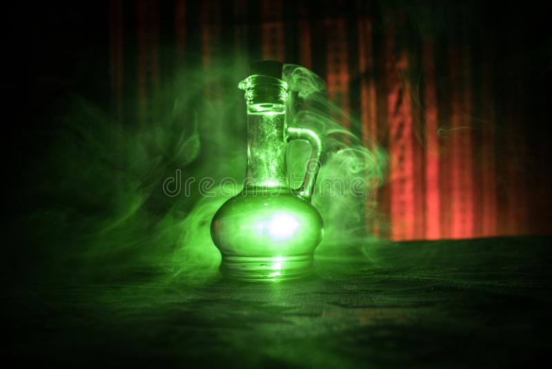 在黑暗的有雾的背景的古董和葡萄酒玻璃瓶与光 毒物或魔术液体概念 库存照片