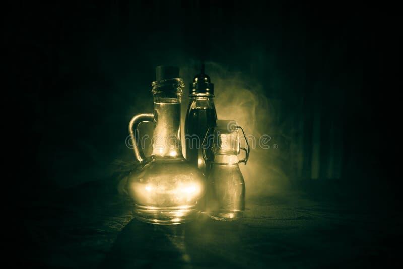 在黑暗的有雾的背景的古董和葡萄酒玻璃瓶与光 毒物或魔术液体概念 图库摄影
