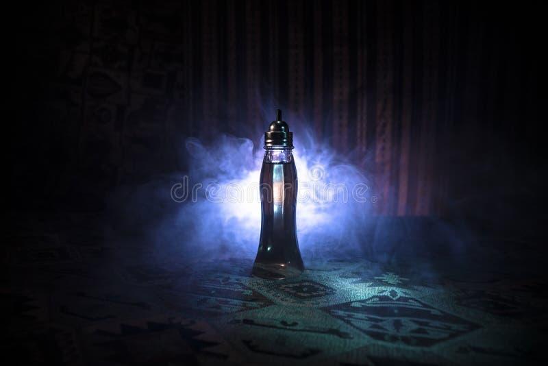 在黑暗的有雾的背景的古董和葡萄酒玻璃瓶与光 毒物或魔术液体概念 免版税库存图片