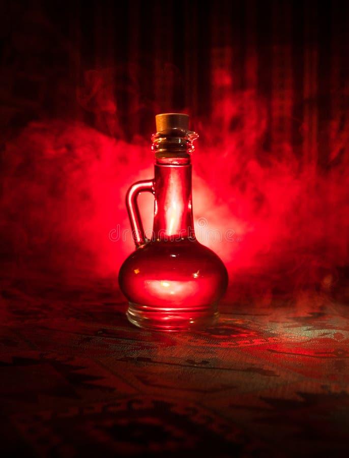 在黑暗的有雾的背景的古董和葡萄酒玻璃瓶与光 毒物或魔术液体概念 免版税库存照片