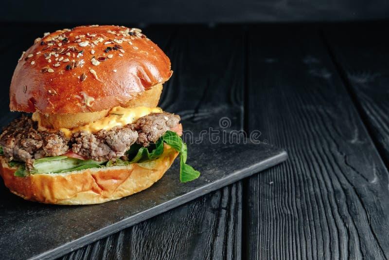 在黑暗的木板的自创水多的汉堡 库存图片