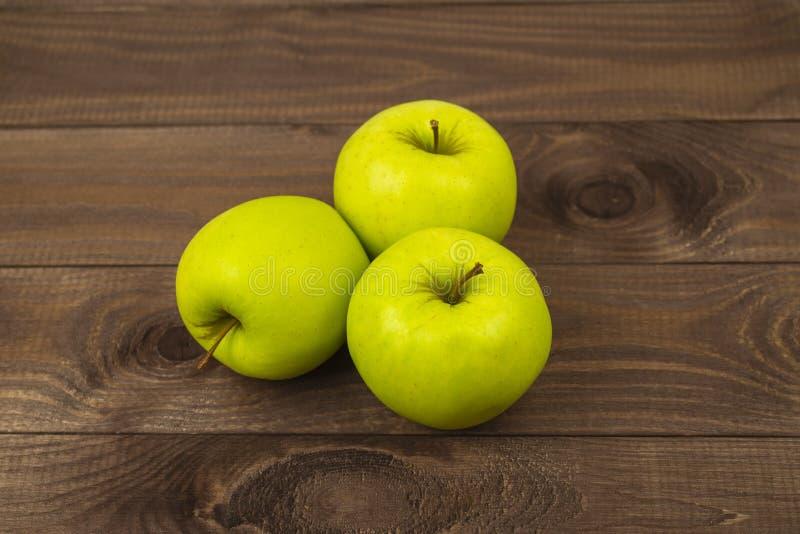 在黑暗的木桌上的三个美味金黄grenni苹果 成熟整个苹果小组堆,鲜美健康果子 免版税库存照片