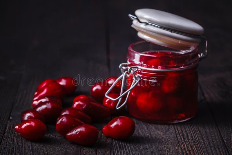在黑暗的木桌上的异常的cornel果酱 库存照片