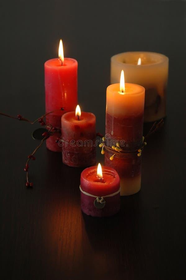 在黑暗的木桌上的浪漫蜡烛 免版税图库摄影