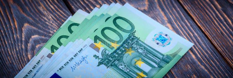 在黑暗的木背景的欧元现金钞票 库存图片