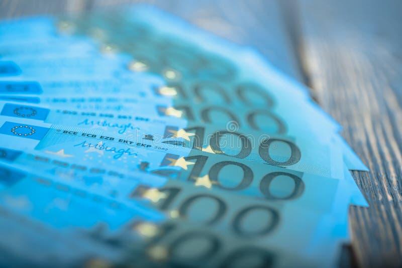 在黑暗的木背景的欧元现金钞票 免版税库存图片