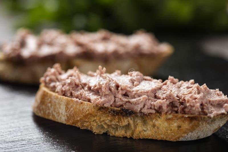 在黑暗的板岩的肝肠三明治 免版税库存照片