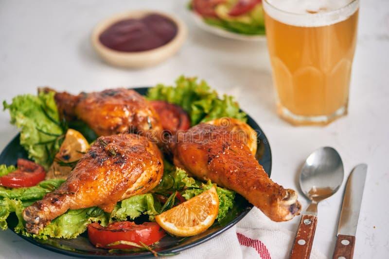 在黑暗的板材的格栅烤的烤鸡腿用在碗和莴苣叶子,玻璃杯子的西红柿酱啤酒 免版税库存图片