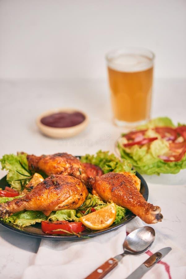 在黑暗的板材的格栅烤的烤鸡腿用在碗和莴苣叶子,玻璃杯子的西红柿酱啤酒 库存图片