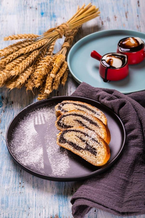 在黑暗的板材的罂粟籽果馅奶酪卷有糖做的叉子剪影的 库存照片