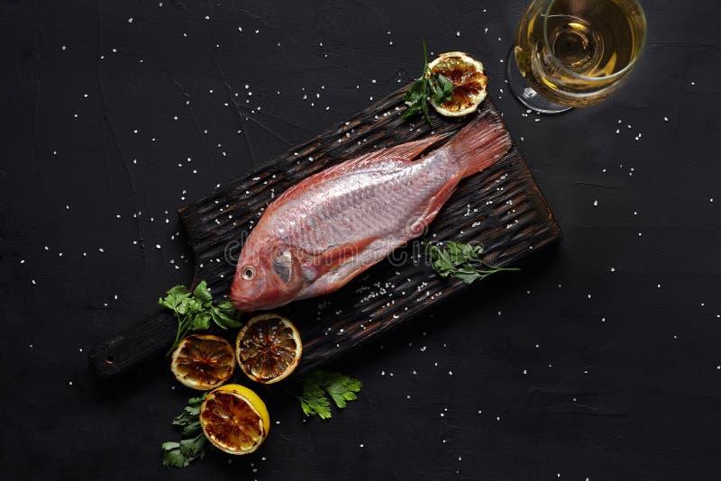 在黑暗的桌,顶视图上的可口新鲜的未加工的红色海鲜鱼梭鱼 免版税库存照片