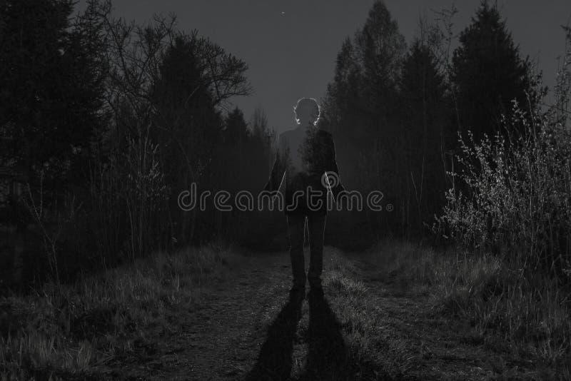 在黑暗的森林路的男性剪影通过灌木夜 供以人员在路的身分反对汽车 库存图片