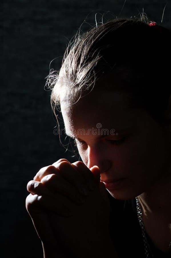 在黑暗的祈祷的年轻女人画象 库存图片