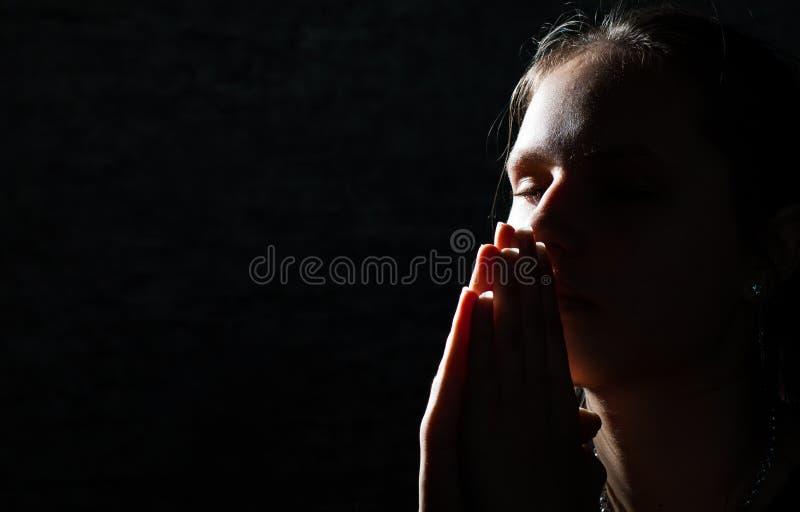 在黑暗的祈祷的年轻女人画象 免版税库存图片