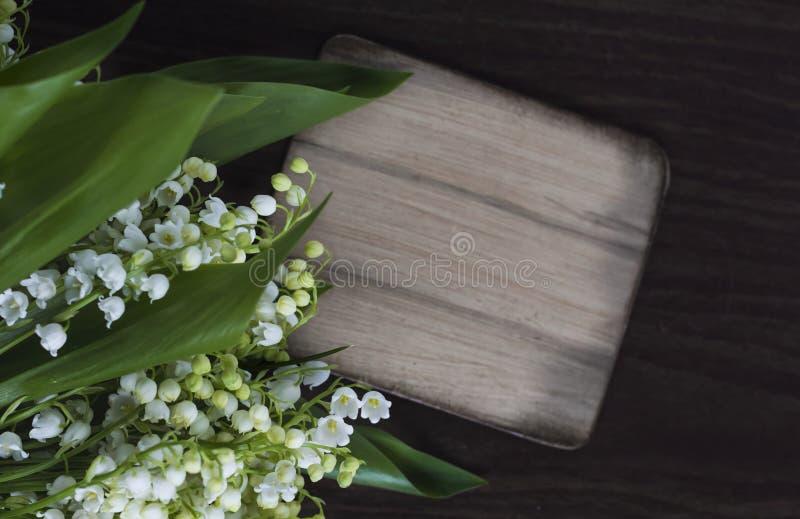 在黑暗的织地不很细背景的美丽的铃兰花与题字的一个标志 免版税库存照片