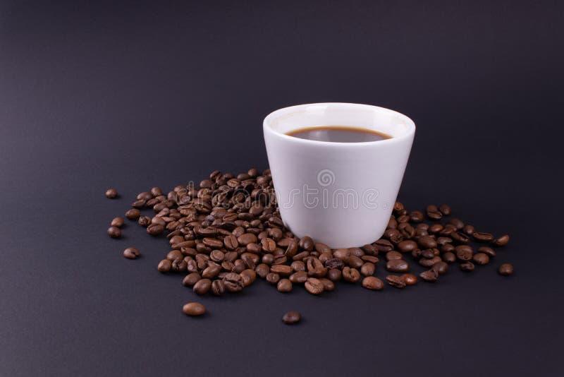 在黑暗的背景一个白色杯子在咖啡豆的浓咖啡 免版税图库摄影