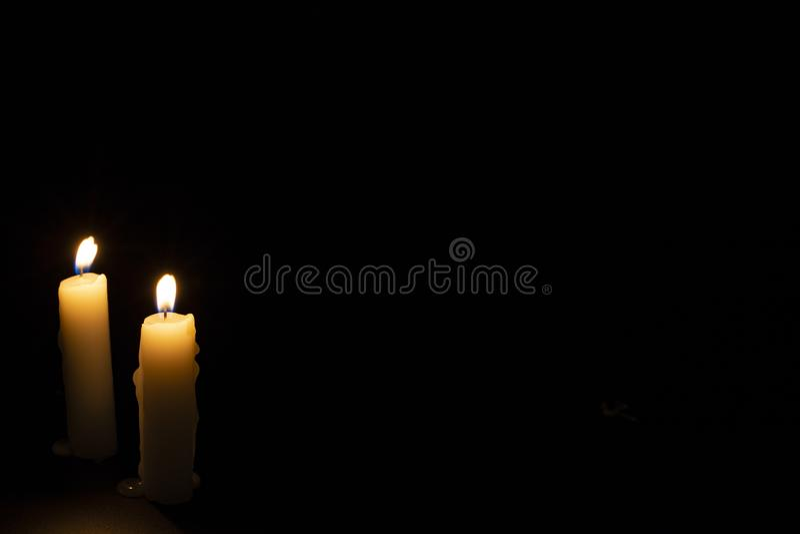 在黑暗的背景的两个蜡烛 点燃在黑色的蜡烛 与温暖的火焰的黄色蜡蜡烛 免版税库存图片