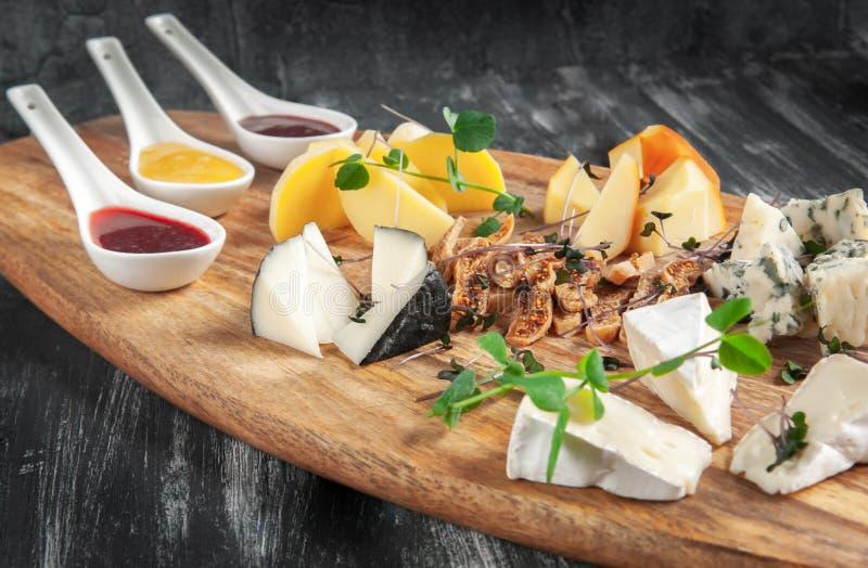 在黑暗的背景的乳酪盘子 装饰了用新鲜的草本和无花果 被弄脏的背景 免版税库存图片