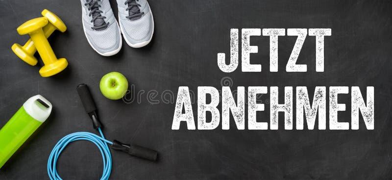 在黑暗的背景的健身设备-丢失重量现在的Jetzt abnehmen德国人 免版税库存照片