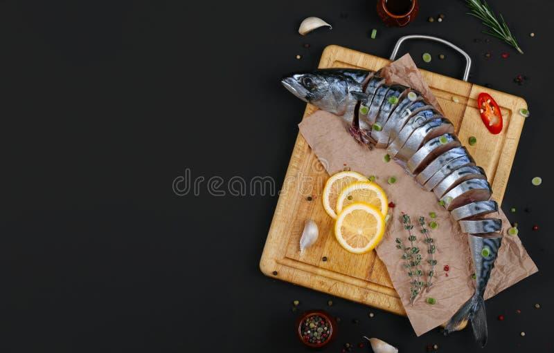 在黑暗的背景的切的鲭鱼与成份 免版税库存照片