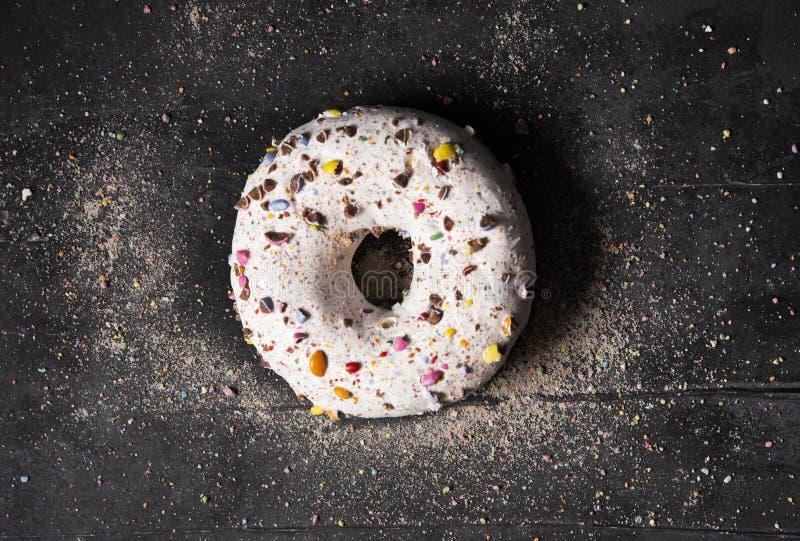 在黑暗的背景的唯一可口多福饼与五颜六色洒概念顶视图 免版税库存图片