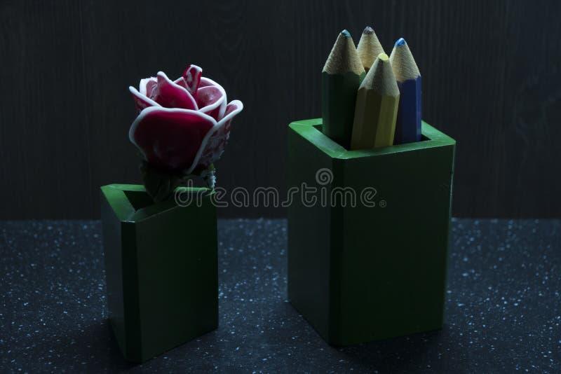 在黑暗的背景的大玫瑰色糖果与在绿色箱子的五颜六色的铅笔 免版税库存照片