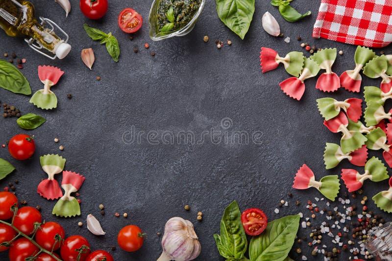 在黑暗的背景的意大利旗子farfalle面团与水平拷贝的空间 西红柿,大蒜,蓬蒿,橄榄油 图库摄影