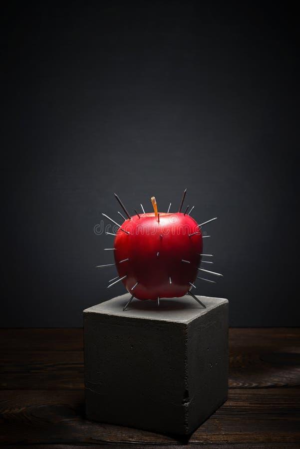 在黑暗的背景的新鲜水果在具体立场 与锋利的刺的水多的红色苹果计算机 库存图片