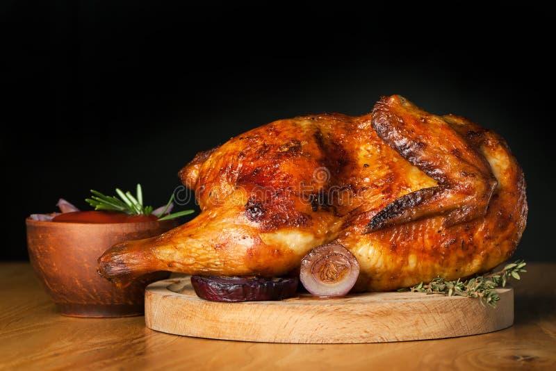 在黑暗的背景的烤鸡 库存图片