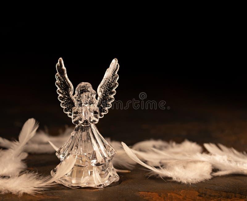 在黑暗的背景的玻璃天使 库存图片