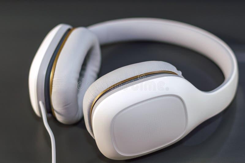 在黑暗的背景的白色耳机 免版税库存图片