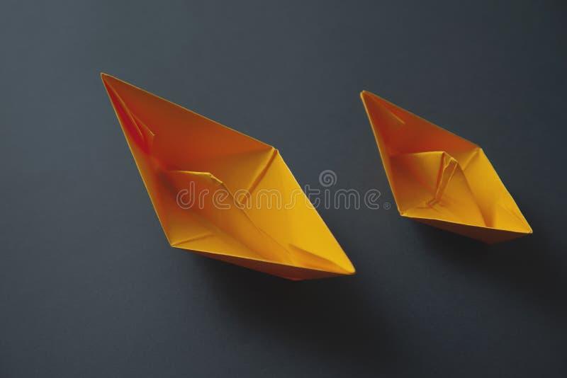 在黑暗的背景的纸小船 免版税库存图片
