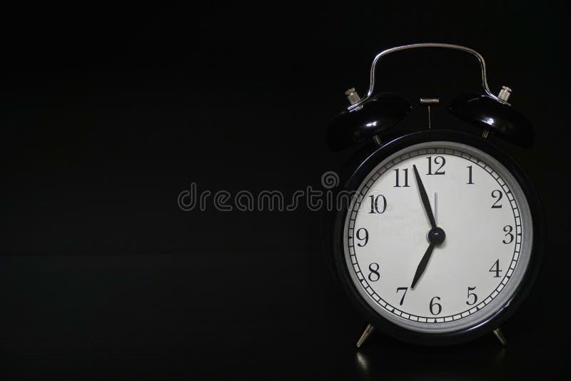 在黑暗的背景的经典机械闹钟 免版税库存照片