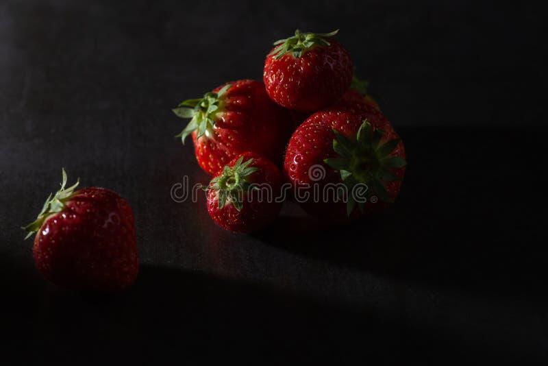 在黑暗的背景的草莓 低调照明设备 免版税库存照片