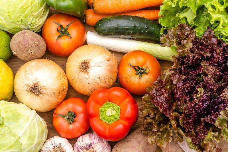 在黑暗的背景的菜 r 黄瓜,圆白菜,沙拉,胡椒,葱,大蒜,红萝卜, 库存照片