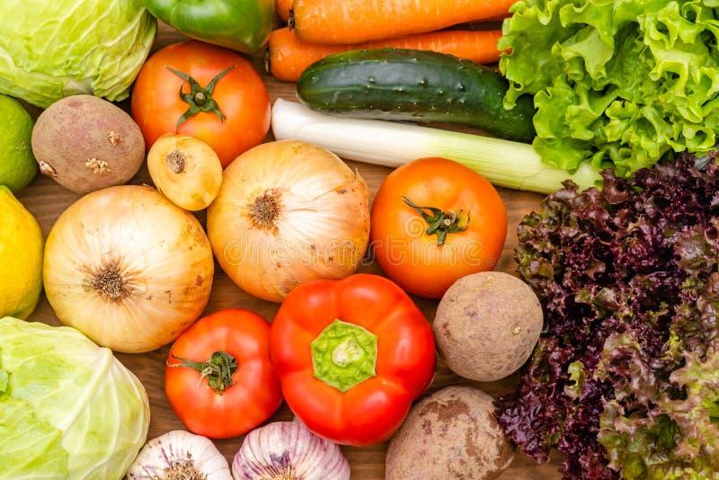 在黑暗的背景的菜 r 黄瓜,圆白菜,沙拉,胡椒,葱,大蒜,红萝卜, 图库摄影